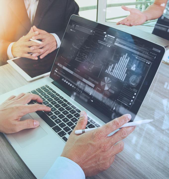 Mehrere Personen arbeiten an einem Laptop