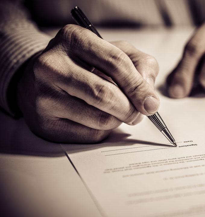 Eine Hand in Großaufnahme unterschreibt einen Vertrag